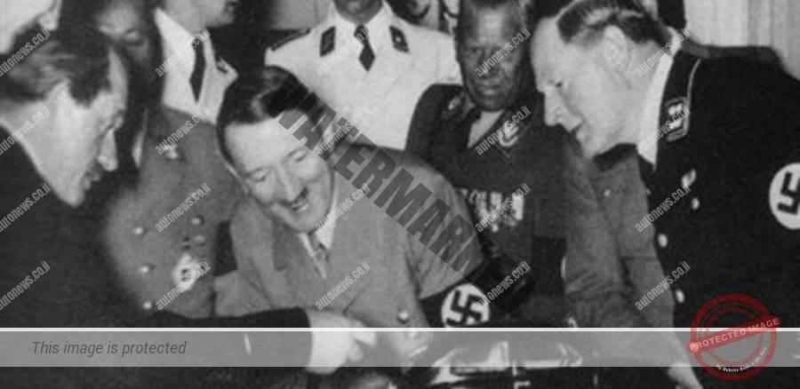 אדולף היטלר, הצורר הנאצי, מוקף בחברי מפלגה, מחייך ומקבל הסבר על דגם של החיפושית ממתכננה, פרופסור פרדיננד פורשה (משמאל) בביגוד אזרחי וללא סממנים נאציים.