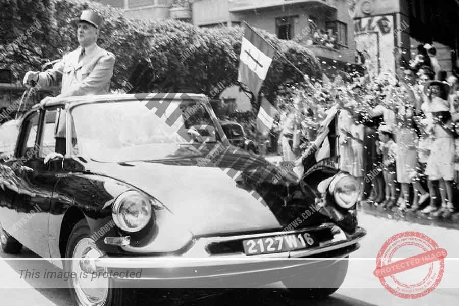 שארל דה גול בסיטרואן DS נשיאותית וללא גג מתנשא גבוה מעל למסגרת הגג