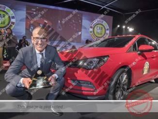 קרל-תומאס נוימאן, הבוס של אופל, מציג את פרס מכונית השנה על רק הזוכה בפרס (אופל)