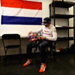 וורסטפאן מכין את הקסדה למרוץ ודגל הולנד תלוי על הקיר