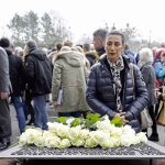 """ד""""ר שרון נזריאן (משמאל) סגנית נשיא בכירה לעניינים בינלאומיים, בליגה למניעת השמצה, מניחה זר פרחים על אנדרטה לזכר עובדי הכפיה במפעלי פולקסווגן במהלך המלחמה"""